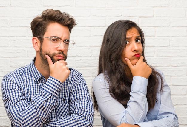 Junge indische frau und kaukasische mannpaare, die oben denken und schauen, verwirrt über eine idee
