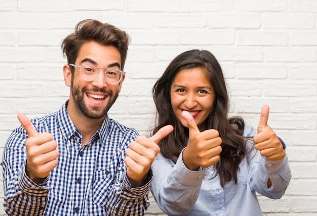 Junge indische frau und kaukasische mannpaare nett und aufgeregt, oben lächelnd, daumen hoch, konzept des erfolgs und zustimmung, okaygeste und anheben