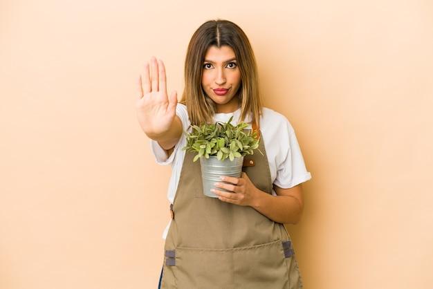 Junge indische gärtnerin, die eine isolierte pflanze hält, die mit ausgestreckter hand steht, die stoppschild zeigt, das sie verhindert.