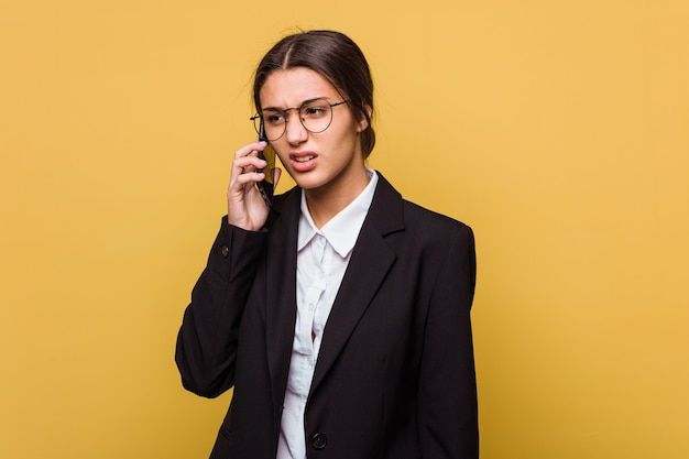 Junge indische geschäftsfrau, die am telefon lokalisiert auf gelbem hintergrund spricht