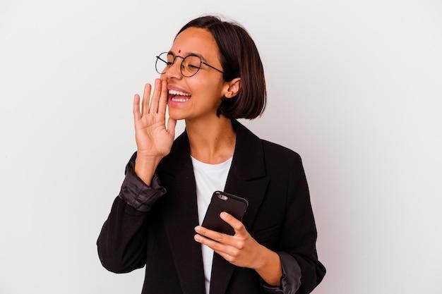 Junge indische geschäftsfrau, die ein telefon hält, isoliert schreit und handfläche nahe geöffnetem mund hält.