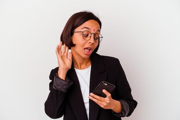 Junge indische geschäftsfrau, die ein telefon hält, lokalisierte den versuch, einen klatsch zu hören.