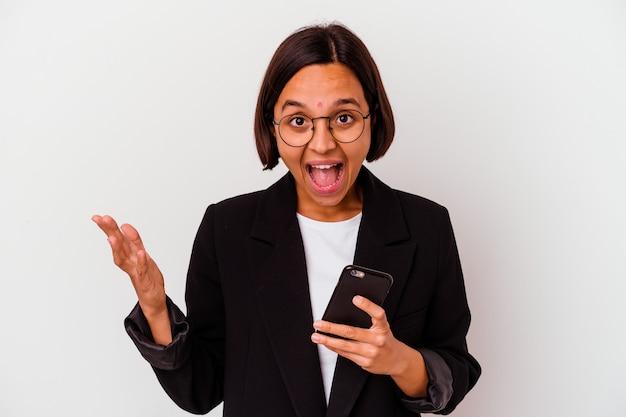 Junge indische geschäftsfrau, die ein telefon isoliert hält junge indische geschäftsfrau, die ein telefon isoliert hält, empfängt eine angenehme überraschung, aufgeregt und hebt die hände.