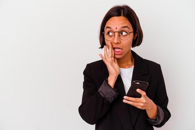 Junge indische geschäftsfrau, die ein telefon isoliert hält, sagt eine geheime heiße bremsnachricht und schaut zur seite