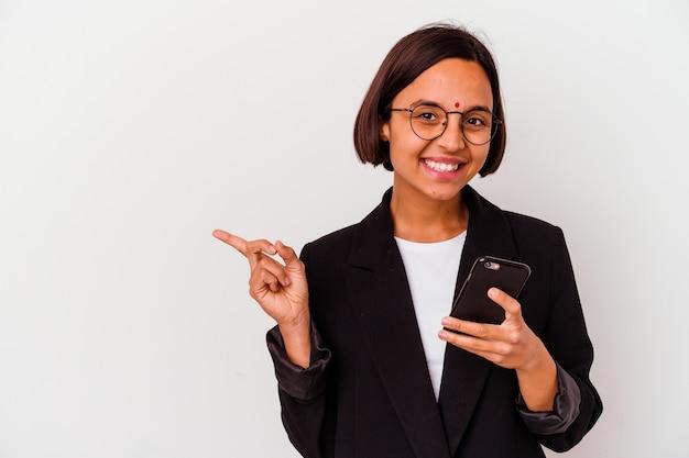 Junge indische geschäftsfrau, die ein telefon lokalisiert, das lächelnd und beiseite zeigt und etwas an der leeren stelle zeigt.