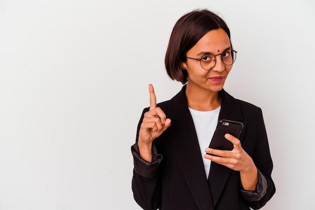 Junge indische geschäftsfrau, die ein telefon lokalisiert hält, das nummer eins mit dem finger zeigt.