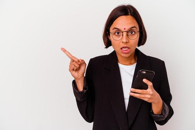 Junge indische geschäftsfrau, die ein telefon lokalisiert hält, das zur seite zeigt