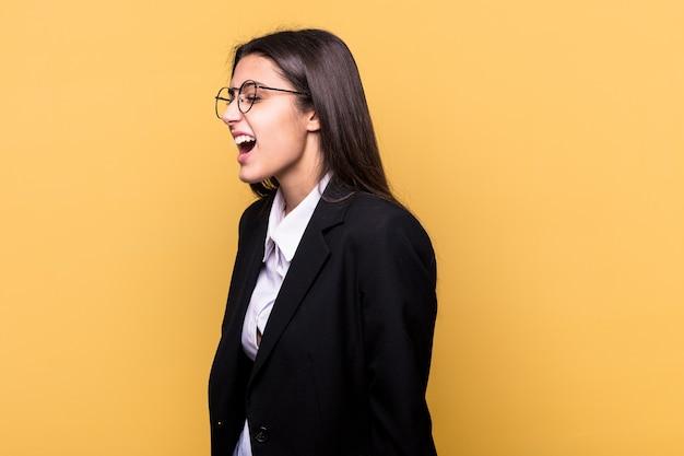 Junge indische geschäftsfrau isoliert auf gelb schreien in richtung eines kopierraums