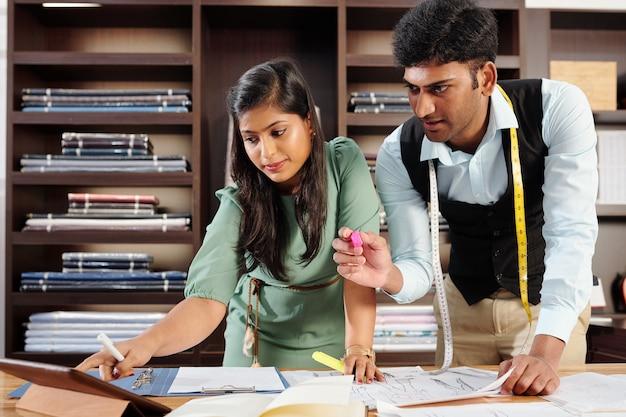 Junge indische schneider arbeiten an modeskizze für kunden