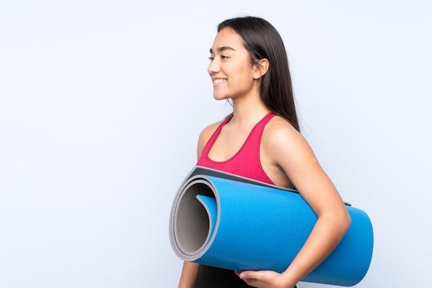 Junge indische sportfrau auf blauer wand mit einer matte