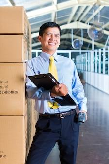 Junge indonesische arbeitskraft im lager mit scanner