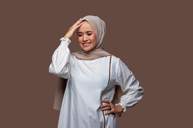 Junge indonesische frau im hijab, die den kopf mit schwindligen ausdrucksstresskopfschmerzen hält