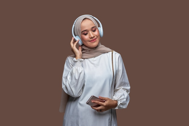 Junge indonesische frau im hijab hört musik mit drahtlosen kopfhörern, während sie ihre augen schließt