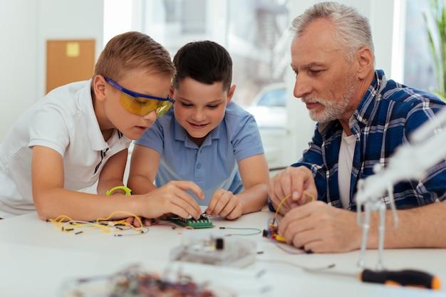 Junge ingenieure. erfreute kluge kinder, die sich das mikroschema ansehen und versuchen zu verstehen, wie es funktioniert