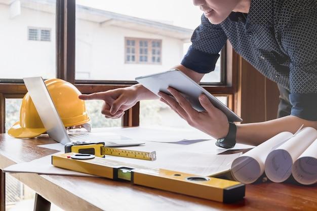 Junge ingenieure verwenden laptop-notebook, um modernes projekt im büro zu entwerfen