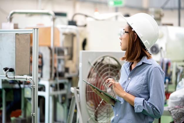 Junge ingenieurfrau überprüft die programmierung in der automatisierungsfabrik.