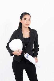 Junge ingenieurin des porträts, die schwarzen anzug trägt, der blaupause und weißen schutzhelm im schussstudio lokalisiert auf weißem hintergrund hält.