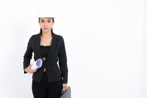 Junge ingenieurin des porträts, die schwarzen anzug und weißen schutzhelm trägt, der blaupause und tasche im schussstudio lokalisiert auf weißem hintergrund hält.
