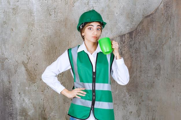 Junge ingenieurin, die eine grüne weste trägt und eine kaffeetasse hält