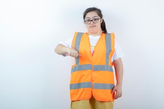 Junge ingenieurin in gläsern, die ihre fäuste auf weißer wand zeigen