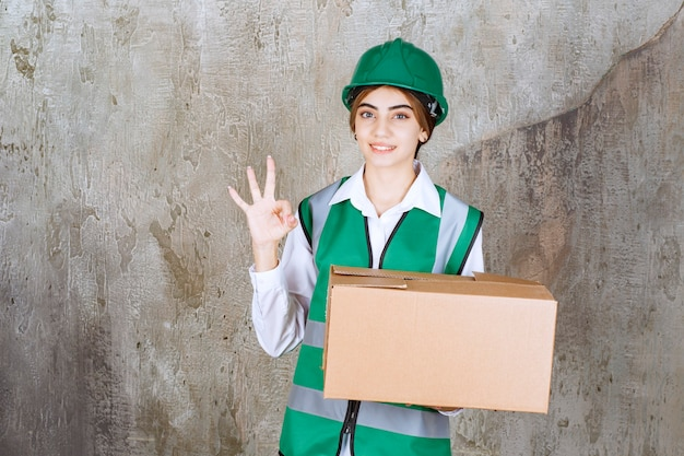 Junge ingenieurin in grüner weste und helm mit pappschachtel, die nummer drei mit der hand zeigt