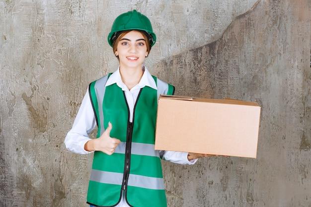 Junge ingenieurin in grüner weste und helm mit pappschachtel mit daumen nach oben