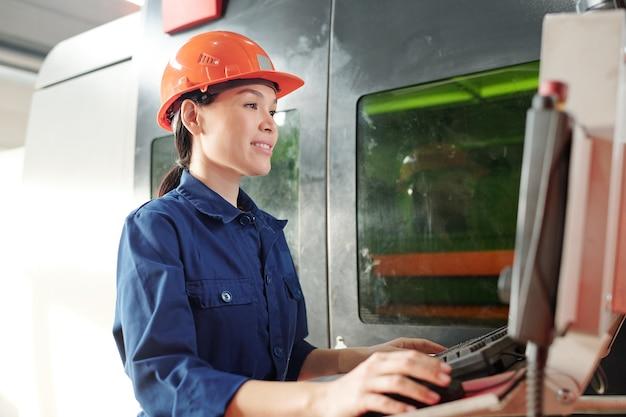 Junge ingenieurin in helm und arbeitskleidung, die maus beim betrachten des bildschirms des monitors oder des bedienfelds klickt