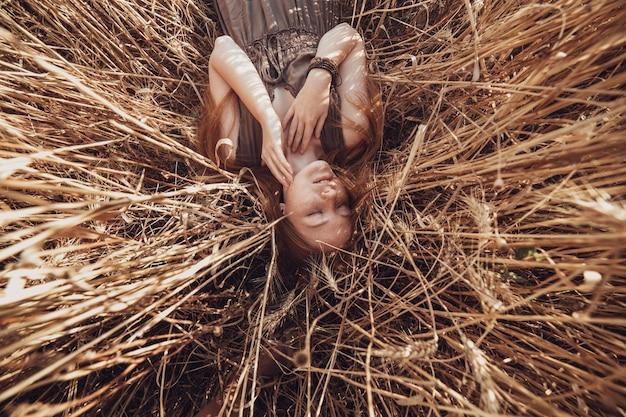Junge ingwerfrau im weizenfeld, das entspannt schaut. weibchen auf einem landwirtschaftlichen gebiet während des sonnenuntergangs.