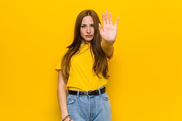 Junge ingwerrothaarigefrau, die mit der ausgestreckten hand zeigt das stoppschild, sie verhindernd steht