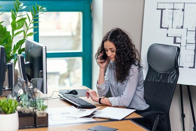 Junge innenarchitektin spricht am smartphone und schaut während des arbeitstages im modernen büro auf die uhr.