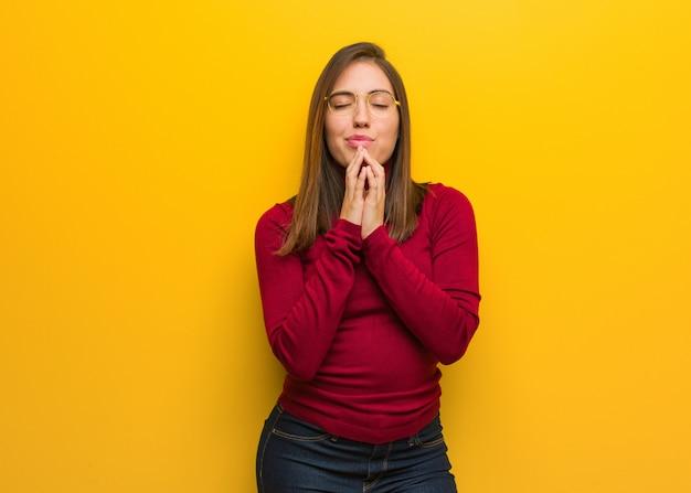 Junge intellektuelle frau, die sehr glücklich und überzeugt betet