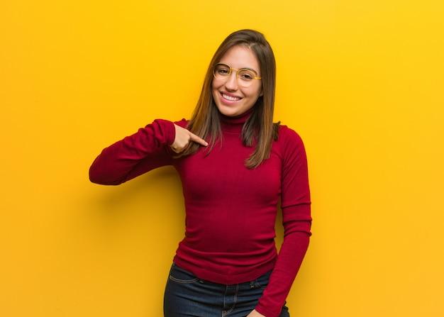 Junge intellektuelle frauenperson, die eigenhändig auf ein hemd copyspace, stolz und überzeugt zeigt
