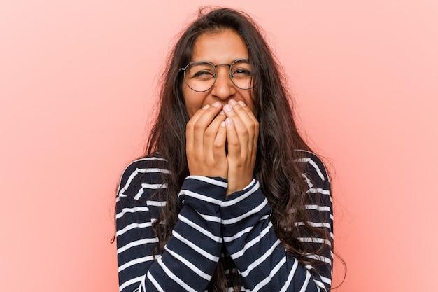 Junge intellektuelle indische frau, die über etwas, mund mit den händen bedeckend lacht.