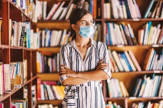 Junge intelligente attraktive studentin mit gesichtsmaske, die in bibliothek mit verschränkten armen steht