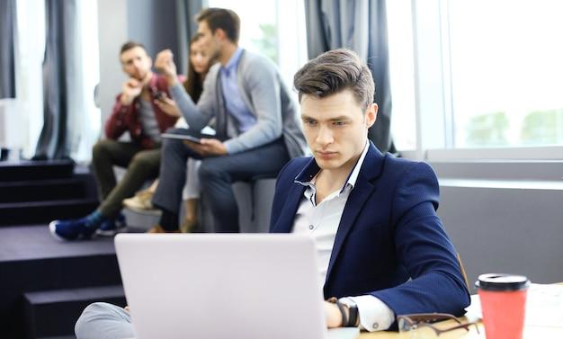 Junge intelligente leute verwenden geräte, während sie im modernen büro hart arbeiten. junger mann, der an seinem laptop arbeitet.