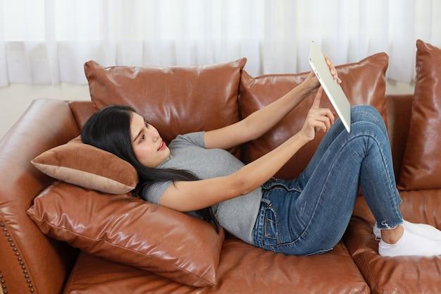Junge intelligente und aktive asiatische frau, die auf dem sofa im wohnzimmer liegt und tablet mit glücklichem lächelndem gesicht benutzt