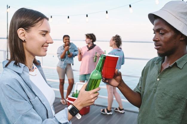 Junge interkulturelle dates klirren mit drinks gegen ihre freunde