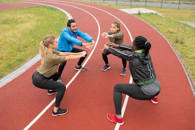 Junge interkulturelle freunde in sportbekleidung strecken ihre arme nach vorne, während sie insgesamt im stadion kniebeugen machen