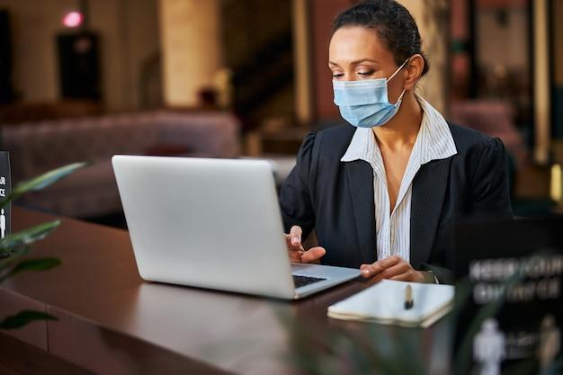 Junge internationale frauen, die während der quarantäne im café arbeiten und eine maske tragen, e-mails lesen