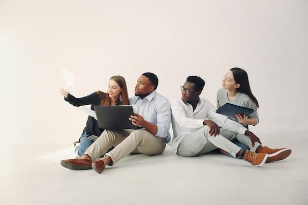 Junge internationale leute, die zusammenarbeiten und den laptop benutzen