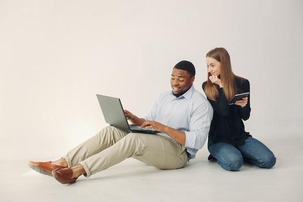 Junge internationale paare, die zusammenarbeiten und den laptop benutzen