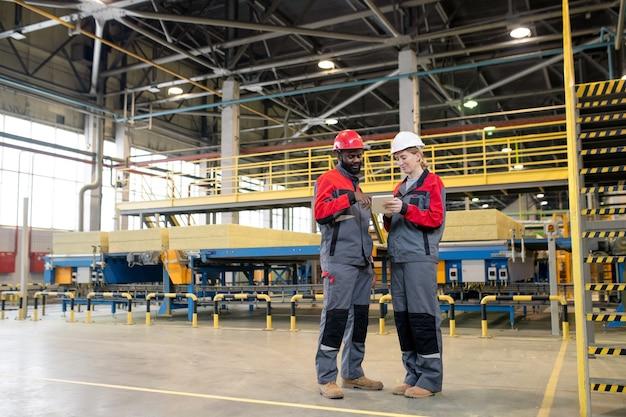 Junge interrassische kollegen in arbeitsschutzkleidung mit tragbarem gerät bei der planung des produktionsvolumens in der fabrik