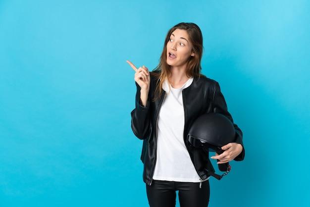 Junge irische frau, die einen motorradhelm lokalisiert auf blauem hintergrund hält, der beabsichtigt, die lösung beim anheben eines fingers zu realisieren