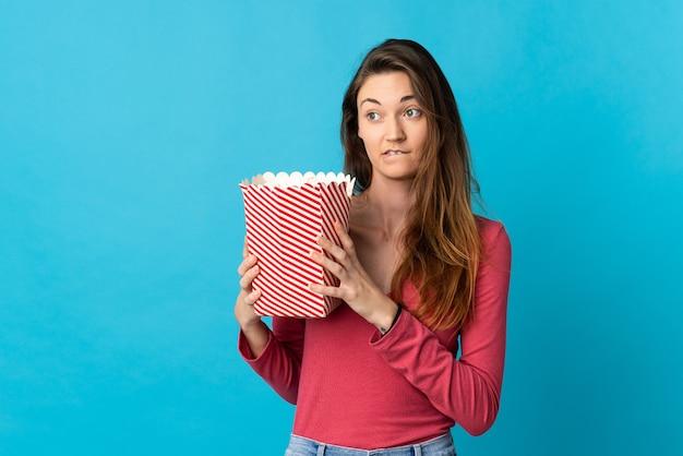 Junge irische frau isoliert, die einen großen eimer popcorn hält