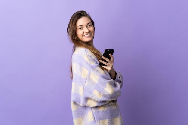 Junge irische frau lokalisiert auf lila hintergrund, der ein mobiltelefon und mit verschränkten armen hält