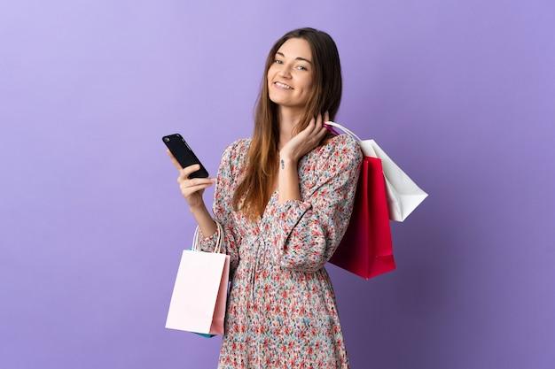 Junge irische frau lokalisiert auf lila hintergrund, der einkaufstaschen hält und eine nachricht mit ihrem handy an einen freund schreibt