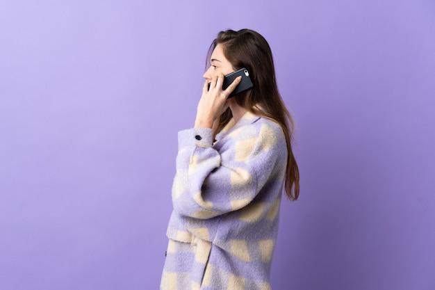 Junge irische frau lokalisiert auf lila hintergrund, die ein gespräch mit dem mobiltelefon mit jemandem hält