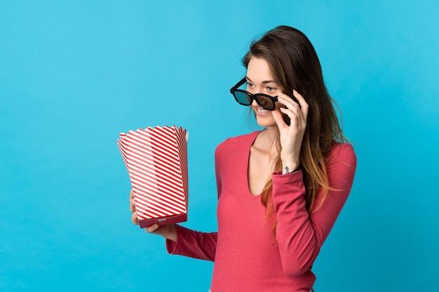 Junge irische frau lokalisiert mit 3d-brille und hält einen großen eimer popcorn
