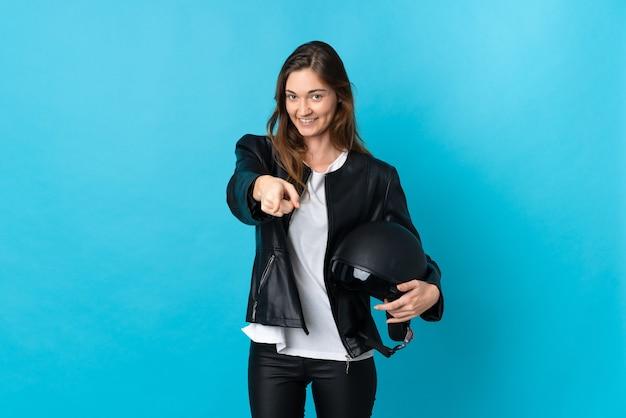 Junge irlandfrau, die einen motorradhelm lokalisiert auf blauer wand hält, die einen finger zeigt und anhebt