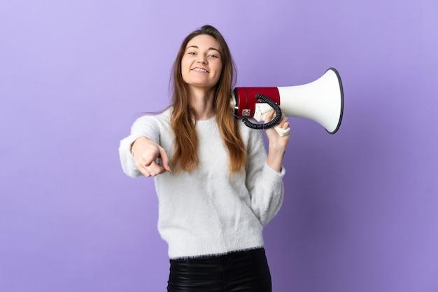 Junge irlandfrau isoliert auf violettem hintergrund, die ein megaphon hält und lächelt, während sie nach vorne zeigt